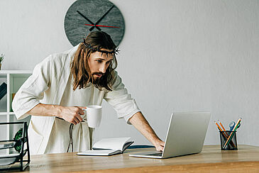 focused Jesus in crown of thorns and robe holding coffee cup and using laptop at table in modern office